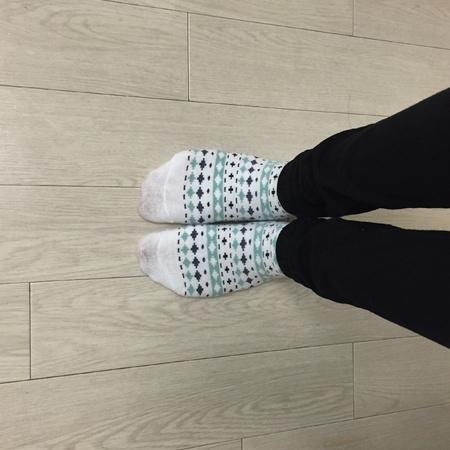 Feet in socks. Woman relaxes.