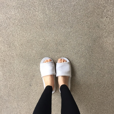 jeans: Close up of a womans white Fluffy slippers Stock Photo
