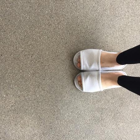 Gros plan des pantoufles moelleuses blanches d'une femme