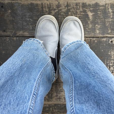 part of me: hombre joven que llevaba zapatos grises y pantalones azules sobre fondo de madera grande para cualquier uso.