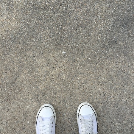 White Sneakers shoes walking on ground top view great for any use.