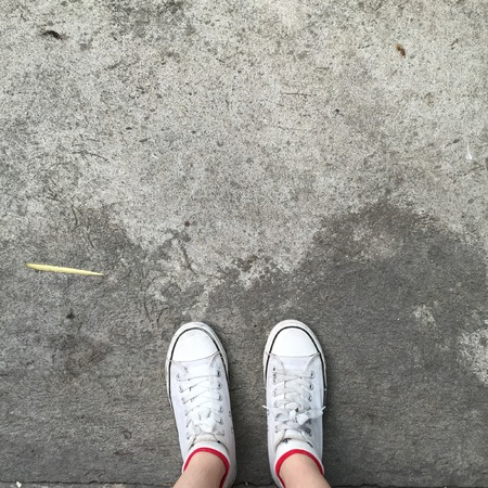 part of me: White Sneakers shoes walking on Dirty concrete top view , Canvas shoes walking on concrete great for any use. Foto de archivo