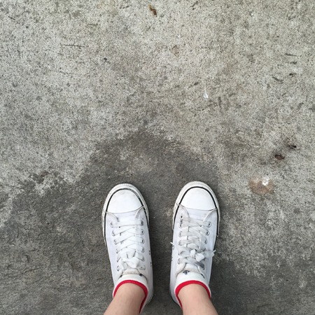 teen feet: White Sneakers shoes walking on Dirty concrete top view , Canvas shoes walking on concrete great for any use. Stock Photo
