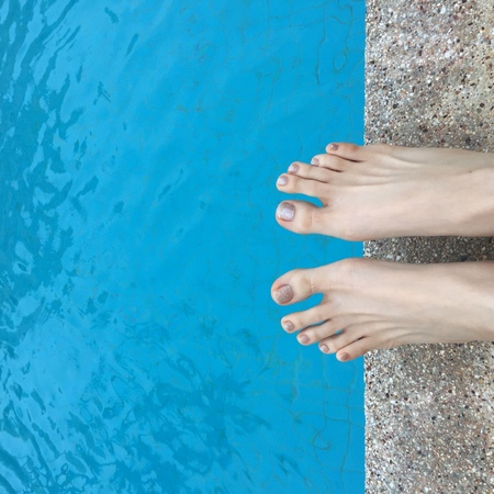 pool side: View of bare female feet at swimming pool side great for any use.