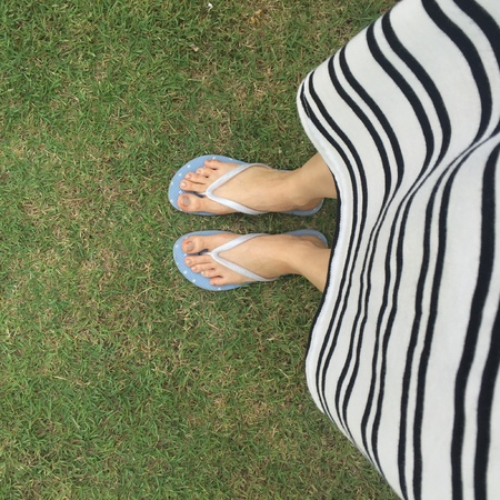 Closeup of bright flip flops and legs on green grass great for any use. Stock Photo