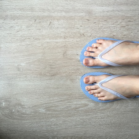 walk board: Low section of woman wearing slippers blue standing on board walk great for any use.
