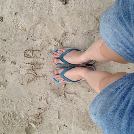 wearing slippers: Woman wearing slippers blue standing on sand great for any use. Stock Photo
