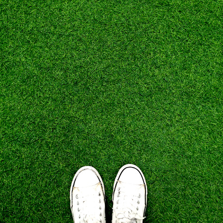 informal: Feet in white sneakers on green grass, top view, informal style great for any use.