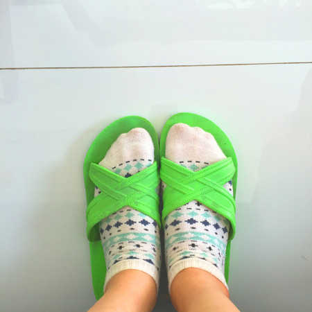flipflops: Selfie feet wearing white polka dot socks and green flip-flops on white floor background great for any use. Stock Photo
