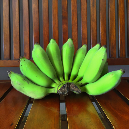 thialand: Green Banana Bundle on a Wood Background Great For Any Use.