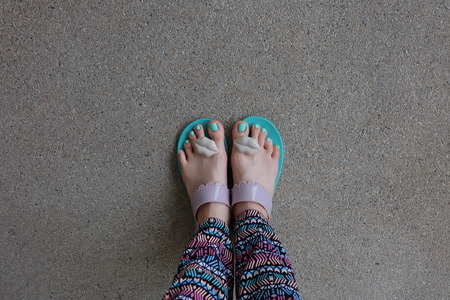 painted toes: Woman Legs And Feet Stand On Ground. A Woman With Flip-Flop Walking Alone On Floor Great For Any Use.  Summer concept holiday,Vintage style.