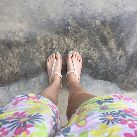 short pants: Female Legs Wearing Flip Flop and Short Pants (Flower) on Ground or Floor. Top View Great For Any Use.