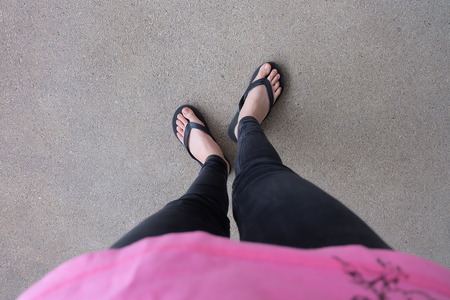 flipflop: Young Girl Legs in Black Flipflop Sandals on Floor or Grunge Great For Any Use.