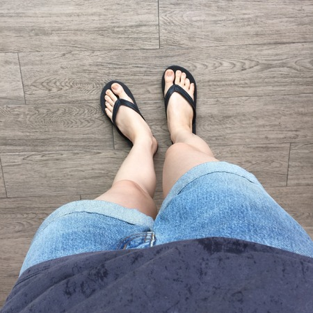 flipflop: Young Girl Legs in Black Flipflop Sandals on Wood Floor Great For Any Use.