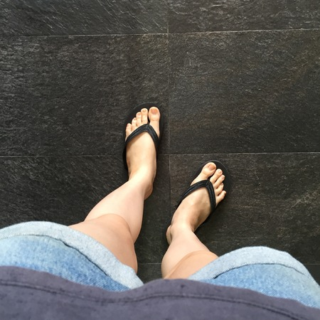 informal clothes: Young Girl Legs in Black Flipflop Sandals on Floor or Grunge Great For Any Use.