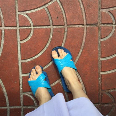 morals: Close up of a Womans Blue Slippers Buddhist Walking on Street or Ground for Relaxation and Meditation Great For Any Use. Stock Photo