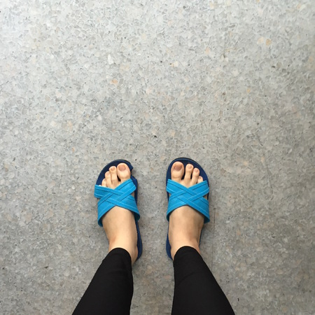 wearing slippers: Woman Wearing Slippers Blue Standing on Ground or Floor Great For Any Use. Stock Photo