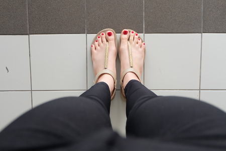 wearing slippers: Female feet wearing slippers or flip-flop outdoor red nail great for any use. Stock Photo