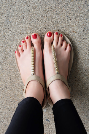 flipflop: Female feet wearing slippers or flip-flop outdoor red nail great for any use. Stock Photo
