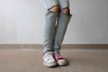 Young Fashion Womans Legs in Blue Jeans and White, Red Sneakers on Floor Great For Any Use. Stock Photo