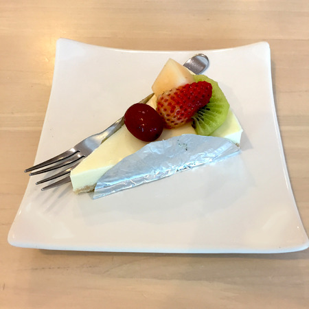 dessert fork: Slice Of Cheesecake Topped With Strawberry, Kiwi, Grap And Cantaloupe Compote On Plate On Wood Table With Dessert Fork Great For Any Use.