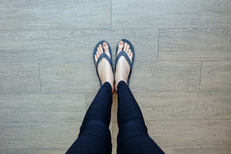 footware: Young Girl Legs in Black Flipflop Sandals on Wood Floor Great For Any Use.