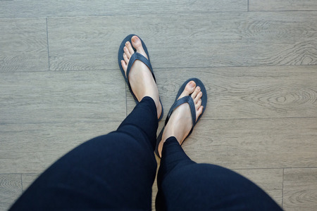 informal clothes: Young Girl Legs in Black Flipflop Sandals on Wood Floor Great For Any Use.