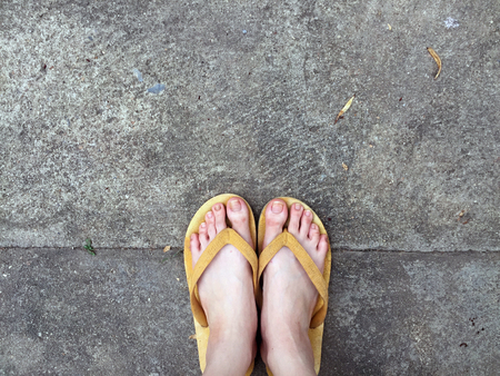 Yellow Sandals on Female Feet on Ground Background Great For Any Use. Reklamní fotografie