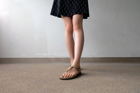 Close up of Slim Legs of Woman Wearing Gold Sandals on Ground Great For Any Use. Stock Photo