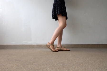 Close up of Slim Legs of Woman Wearing Gold Sandals on Ground Great For Any Use. Banco de Imagens