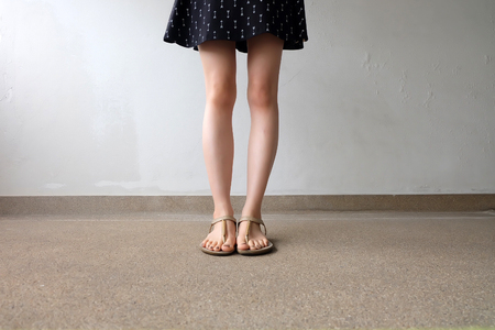 Close up of Dress and Slim Legs of Woman Wearing Gold Sandals on Ground Great For Any Use. Stock Photo