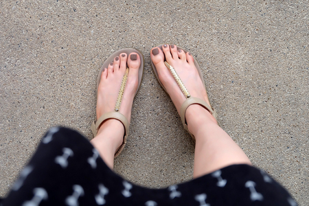 Selfie Feet Wearing Gold Sandals and Dress on Ground Background Great For Any Use. Stock Photo