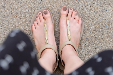 Selfie Feet Wearing Gold Sandals and Dress on Ground Background Great For Any Use. Stock Photo - 76107137
