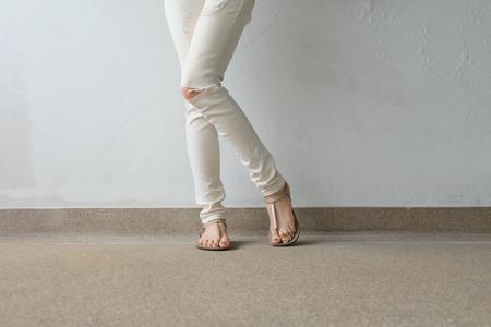 任意の使用のための地面、屋外背景素晴らしい黄金のサンダル女性脚。