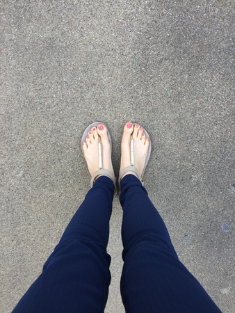 Close Up Feet with Brown Nail in Gold Sandals and Blue Pants on Female Feet on Ground Background Great For Any Use.