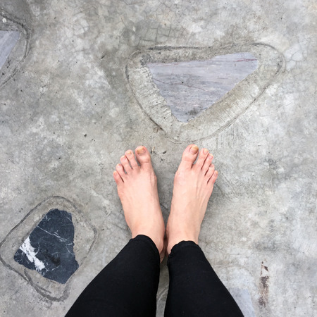 Close Up of Girl Barefeet On The Concrete Stone Tiles Floor Background Great For Any Use.