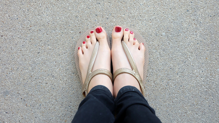 Close Up on Girls Feet Wearing Golden Sandals on Ground Background Great For Any Use.