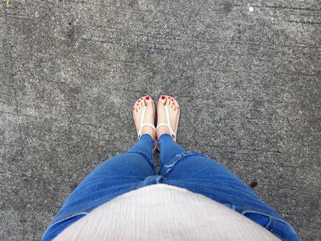 サンダルとブルー ジーンズ女性でコンクリート床背景素晴らしいの任意使用の爪の赤と素足のクローズ アップ。