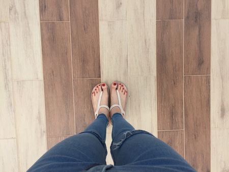 Close-up van blote voeten met rode nagel in sandalen en spijkerbroek Vrouw op de tegel achtergrond Geweldig voor elk gebruik.