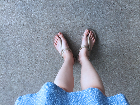 Female Feet Wear Sandals and Blue Dress on the Street Great For Any Use. 版權商用圖片