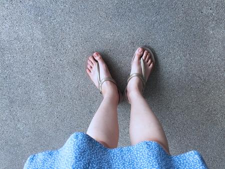 Vrouwelijke voeten dragen sandalen en blauwe jurk op de straat, ideaal voor elk gebruik.