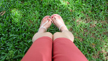 Close Up on Girls Feet Wearing Sandals on Green Grass Great For Any Use.