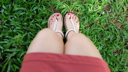 woman sandals: Close Up on Girls Feet Wearing Sandals on Green Grass Great For Any Use.