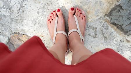모든 사용에 대 한 훌륭한 시멘트에 샌들과 빨간 손톱을 착용하는 여자의 피트 닫습니다. 스톡 콘텐츠