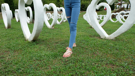 Feet Selfie in Sandals Standing on Green Grass with White Heart Shape Artificial Background Great For Any Use. Stock Photo