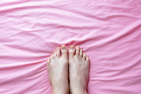 footcare: Close Up of Female Feet and Slim Legs on the Pink Bed, Feet in the Bedroom Background at Home Great For Any Use.