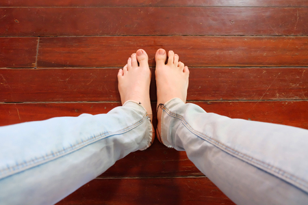 Close Up Woman Barefoot Wear Blue Jeans on Wooden Floor Background Great For Any Use. Stock Photo
