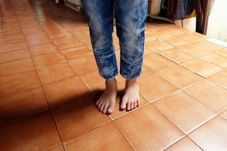 Close Up Boy Barefoot Wear Blue Jeans on Tile Background Great For Any Use.