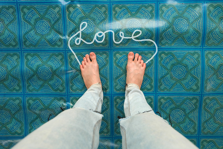 Selfie Womans Bare Feet with Word Love on Linoleum Background Great For Any Use. Stock Photo