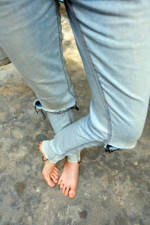 Barefeet Selfie Wear Blue Jeans on Old Concrete Background Great For Any Use. 免版税图像